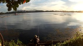 Man use fishing rod to catch fish on a lake at sunset. San Pablo City, Laguna, Philippines - August 2, 2015: Man use fishing rod to catch fish on a lake at stock footage