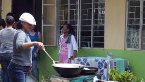 Parents of public elementary school children saut`e vegetables during the nutritional cooking meet. San Pablo City, Laguna, Philippines - August 2, 2015: Parents stock footage