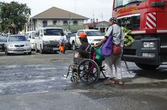 Blind man pushing wheelchair of disabled beggar. San Pablo City, Laguna, Philippines - December 3, 2016: Blind man pushing wheelchair of disabled beggar Stock Photography