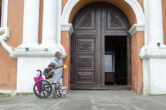 Lady, Blind Man beside disabled Beggar in wheelchair at Church yard Gate Portal. San Pablo City, Laguna, Philippines - December 3, 2016: Lady, Blind Man beside Royalty Free Stock Photo