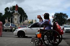 Wheelchair beggar holding Christmas gift box seeking alms at church gate portal. San Pablo City, Laguna, Philippines - December 21, 2016: wheelchair beggar royalty free stock photos