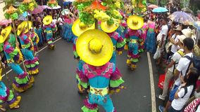 Backside of young men and women in ornate coconut costume parades along the street, a festival to honor a patron saint. San Pablo City, Laguna, Philippines