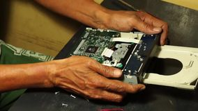 Technician placing back the front  cover casing of DVD Optical Drive. San Pablo City, Laguna, Philippines - January 24, 2014: Technician placing back the front stock video