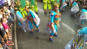 Young men and women in ornate butterfly costume dance along the street, a festival to honor a patron saint. San Pablo City, Laguna, Philippines - January 13