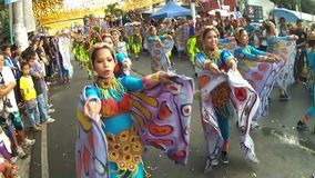 Young women in ornate butterfly costume dance along the street, a festival to honor a patron saint. San Pablo City, Laguna, Philippines - January 13, 2014: Young