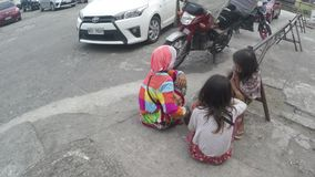 Indigenous girls sitting on pavement beg for alms at church premises