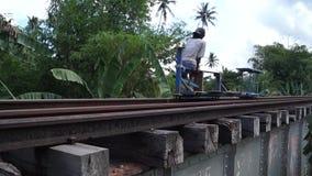 Railroad trolley operator drives foot driven passenger cart. San Pablo City, Laguna, Philippines - November 5, 2012: railroad trolley operator drives foot driven stock video footage