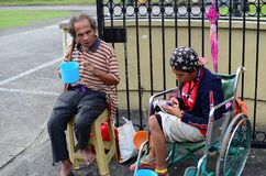Beggar on wheelchair using cellphone. San Pablo City, Laguna, Philippines - October 20, 2016: Blind Man beside disabled Beggar in wheelchair at Church yard Gate Stock Images