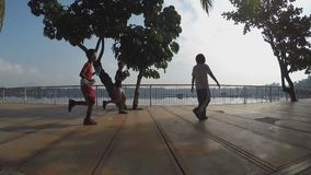 Girl boy run at lake-shore boardwalk. Silhouettes. San Pablo City, Laguna, Philippines - October 8, 2015: Girl boy run at lake-shore gazebo view deck boardwalk stock video footage