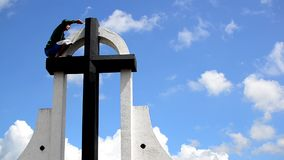 Man cleans and paints huge tall cross on sepulcher tomb stock footage