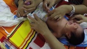 Pediatrician checkup and clean baby umbilical cord. San Pablo City, Laguna, Philippines - October 8, 2015: Pediatrician performing post natal medical examination stock footage
