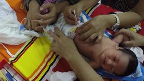 Pediatrician checkup and clean baby umbilical cord. San Pablo City, Laguna, Philippines - October 8, 2015: Pediatrician performing post natal medical examination stock video footage