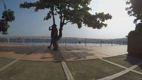 Two men walk lake shore gazebo. Silhouettes. San Pablo City, Laguna, Philippines - October 8, 2015: Two men walk lake shore gazebo view deck boardwalk as their stock video footage