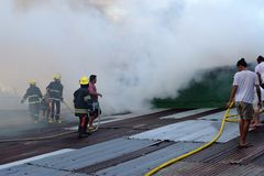 Firemen and volunteers on rooftop put out fire using fire hose during house fire that gutted interior shanty houses stock photo