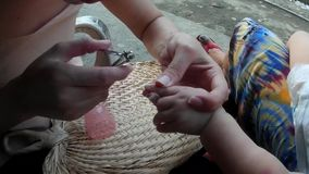 Grand Mother trimming baby`s fingernails. San Pablo City, Laguna, Philippines - September 9, 2015: Grand Mother trimming fingernail of a baby girl with nail stock video footage