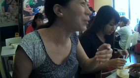 Pretty woman having mouthful eating big meal. San Pablo City, Laguna, Philippines - September 9, 2015: Ladies eating in a fast food restaurant covers mouth stock video footage