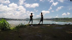 2 two boys fishing on lake shore. Tracking shot. San Pablo City, Laguna, Philippines - September 8, 2015: Man use fishing rod to catch fish on a lake. tracking stock video