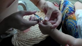 Mother trimming baby`s fingernails. San Pablo City, Laguna, Philippines - September 9, 2015: Mother trimming fingernail of a baby girl with nail clipper stock video