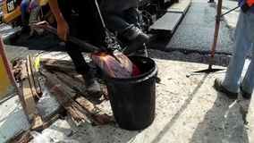 Worker cleaning asphalted spade on street. San Pablo City, Laguna, Philippines - September 21, 2016: Worker cleaning asphalted spade on street stock video