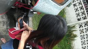 Lady text messaging by smartphone. San Pablo City, Laguna, Philippines - September 9, 2015: Young lady spends lots of her time texting with her smartphone stock video