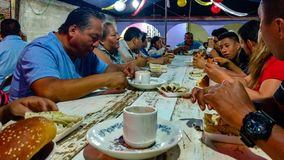 Calenda San Pedro in Oaxaca, Mexico. SAN PEDRO APOSTAL, OAXACA-July 1, 2016. A Mexican family shares a meal of steamed tacos, hot cocoa and bread during the royalty free stock image