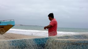 San Pedro, Ecuador - 20180915 - Low View of Man Standing on Beach Next to Boat and Repairing Net. stock video