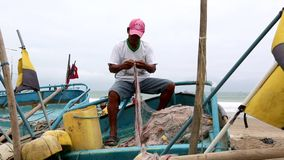 San Pedro, Ecuador - 20180915 - Man Repairs Net While Sitting In Boat. stock video footage