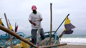 San Pedro, Ecuador - 20180915 - Man Stands in Boat As He Fixes Net. stock footage