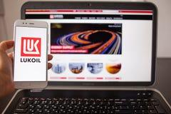 SAN PIETROBURGO, RUSSIA - 14 MAGGIO 2019: Sito Web e logo del lukoil russo della società sugli schermi degli aggeggi fotografia stock libera da diritti