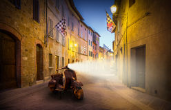 San Quirico D'orcia by night, Tuscany. Beautiful street of tuscan San Quirico D'orcia town by night with old-fashioned scooter Royalty Free Stock Photos