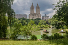San Remo Apartments Lake of Central Park New York City. People paddling in wood boats on The Lake of Central Park with its trees and the San Remo Apartments twin Stock Photography