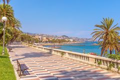 San Remo, Italy – June 24, 2018: Corso dell`Imperatrice pedestrian promende street in San Remo with wiew of the beach and city. Panorama royalty free stock image