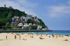 SAN SEBASTIAN, SPAIN - JULY 24, 2018: Ondarreta beach in a sunny day. Igeldo hill in background. San Sebastian or Donostia is a coastal city and municipality royalty free stock photo