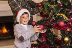 San und Vater, die den Weihnachtsbaum verzieren Lizenzfreie Stockbilder