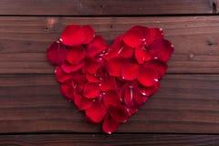 San Valentino: petali rosa a forma di di amore rosso Fotografia Stock