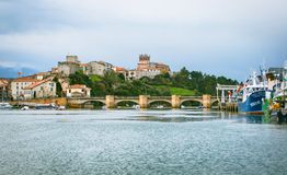 San Vicente de la Barquera, Cantabria. Panoramic of a maritime village and fisherman with church, castle and fishing port royalty free stock image