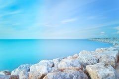 San Vincenzo harbor rocks Long exposure. Italy. San Vincenzo Marina harbor breakwater rocks bay. Long exposure photography. Sea travel destination, Tuscany Stock Photos