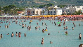 People having fun and bath at the sea of the beach of the italian village stock video
