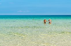 Happy elderly couple enjoys a romantic walk in the crystal clear water on the San Vito Lo Capo beach. Stock Image