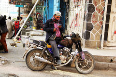 SANAA, YEMEN - 21 DE DICIEMBRE: Sentada yemení joven en una motocicleta, el 21 de diciembre de 2014 en Sanaa Fotografía de archivo libre de regalías