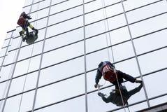 Sanacja pracownicy czyści szklanego fasadowego hotel zdjęcia stock