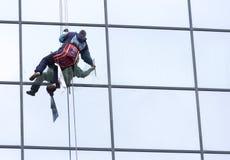 Sanacja pracownik czyści szklanego fasadowego hotel obraz stock