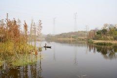 Sanacja pracownika paddling łódź wzdłuż rzeki w pogodnym zimy afte zdjęcia royalty free