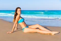 Séance de touristes de brune dans le bronzage de sable de plage heureux Photo stock