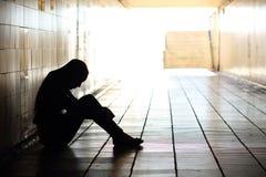 Séance diminuée par adolescent à l'intérieur d'un tunnel sale Images stock