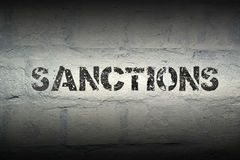 Sanctions word gr. Sanctions stencil print on the grunge white brick wall royalty free stock photography