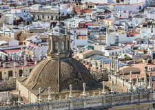 The Sanctuary of the Cathedral (Iglesia del Sagrario) of Seville. Image of the tower of The Sanctuary of the Cathedral of Seville in front of a rooftops view in Stock Photo