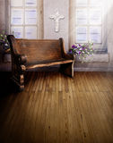 Sanctuary church pew. An old church bench pew on a wooden floor in a sanctuary room with bright light and a cross on the wall. Concept for praying, solace or a stock images