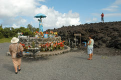 Sanctuary of the lava eruption on La Reunion island. La Reunion island, France - 29 December 2002: people visiting the statue of Godmother with umbrella at the Stock Photos