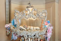 Sanctuary of Vicoforte, holy doll in white cradle with ribbons in Piedmont, Italy. Vicoforte, Italy - August 17, 2016: Sanctuary of Vicoforte, holy doll in white stock images